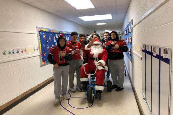 SHHS Varsity Football team escorts Santa to JP.