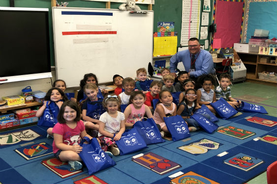 School Superintendent Borsari delivers literacy bags to children.